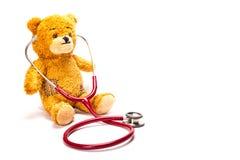 与听诊器和瑞士法郎的玩具熊 免版税图库摄影