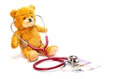 与听诊器和瑞士法郎的玩具熊 免版税库存照片