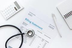 与听诊器和计算器的医疗treatmant布告声明在白色背景顶视图嘲笑 免版税库存图片