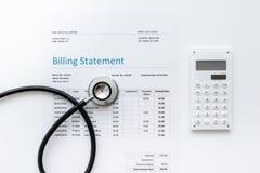 与听诊器和计算器的医疗treatmant布告声明在白色背景顶视图 免版税库存照片