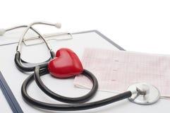 与听诊器的心电图和在桌上的红色心脏 图库摄影