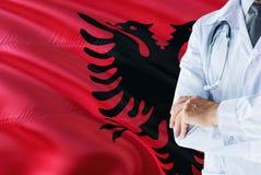 与听诊器的阿尔巴尼亚医生身分在阿尔巴尼亚旗子背景 全国卫生保健系统概念,医疗题材 免版税库存图片
