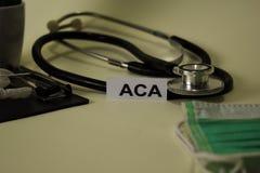 与启发和医疗保健/医疗概念的ACA在书桌背景 库存图片