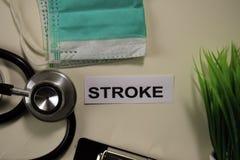 与启发的冲程和医疗保健/医疗概念在书桌背景 免版税库存照片
