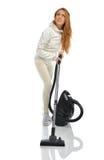与吸尘器的年轻愉快的妇女清洁家地板 免版税库存照片