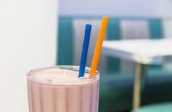 与吸管的一块草莓奶昔玻璃 库存照片