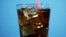 与吸管的混合的可乐鸡尾酒 玻璃有很多泡沫腾涌的饮料冰块 股票录像
