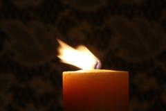 与吹在微风的火焰的蜡烛 免版税库存照片