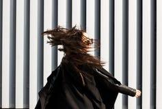 与吹在风的头发的愉快的深色的模型走在Th 库存照片