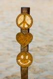 与和平、心脏和面带笑容的木标志在海滩在秘鲁 图库摄影