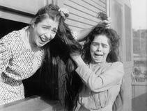 与和拉扯每其他战斗的两名妇女头发(所有人被描述不更长生存,并且庄园不存在 供应商warran 免版税库存图片