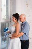 与和播放婚礼礼服结婚的年轻夫妇婚礼乐队和非常愉快 免版税库存图片
