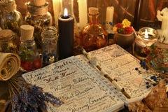 与咒语、淡紫色束和黑蜡烛的不可思议的书在巫婆桌上 免版税库存图片