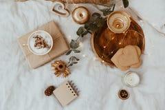 与咖啡杯、曲奇饼和金装饰的背景在床上 免版税图库摄影