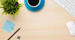 与咖啡杯、计算机和花的办公室桌 免版税库存照片
