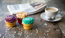 与咖啡杯和报纸的杯形蛋糕 免版税库存图片