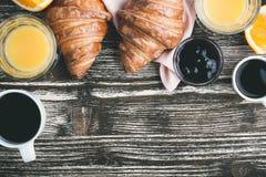 与咖啡杯和橙汁在一张木桌上, t的新月形面包 免版税库存图片