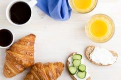 与咖啡杯和橙汁的新月形面包在一张白色桌上, 库存图片