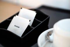 与咖啡杯和水壶的白糖小包在旅馆客房设置了 免版税图库摄影