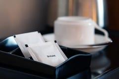 与咖啡杯和水壶的白糖小包在旅馆客房设置了 图库摄影