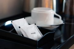 与咖啡杯和水壶的白糖小包在旅馆客房设置了 库存照片