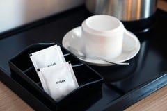 与咖啡杯和水壶的白糖小包在旅馆客房设置了 库存图片