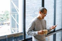 与咖啡杯的快乐的亚洲男性小企业主在搜寻在电话的手上,读接踵而来的sms消息在智能手机w 库存图片