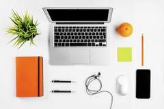与咖啡杯的现代工作区,智能手机、纸、笔记本、片剂和膝上型计算机复制在白色颜色背景的空间 平的位置 免版税库存图片