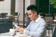 食用英俊的年轻白种人的人坐在咖啡馆使用手机和咖啡 与咖啡的亚洲男性和读书文本 免版税库存照片