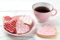 与咖啡的心脏曲奇饼在白色木背景的 免版税库存照片
