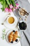 与咖啡的早晨早餐、新月形面包、新鲜的莓果和桃红色开花郁金香 免版税库存照片