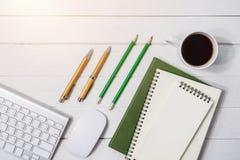 与咖啡的木白色办公桌桌,笔记本,笔 库存图片
