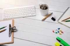 与咖啡的木白色办公桌桌,笔记本,笔 免版税库存照片