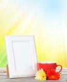 与咖啡的照片框架和大丁草开花 免版税库存照片