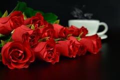 与咖啡的红色玫瑰在晚上 免版税库存照片
