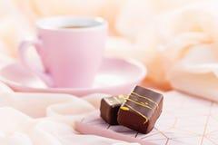 与咖啡的豪华糖果在粉红彩笔背景的 免版税库存照片