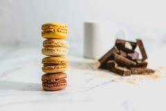 与咖啡的鲜美甜macarons在背景的 免版税图库摄影