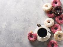 与咖啡的Sone桃红色和白色油炸圈饼在灰色石te的 库存照片