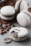 与咖啡豆的法国蛋白杏仁饼干 r 在灰色口气的蛋白杏仁饼干 在灰色石头的法国崩溃macarons 免版税库存图片