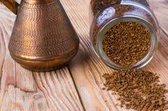 与咖啡豆的被翻转的cezve,碗用在木桌上的碾碎的咖啡 免版税库存图片