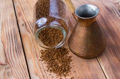 与咖啡豆的被翻转的cezve,碗用在木桌上的碾碎的咖啡 免版税图库摄影