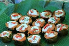 与咖喱酱的被蒸的鱼和洒在上面与椰奶和红色辣椒在香蕉叶子杯子 免版税库存图片