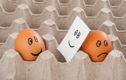 与哀伤的面孔展示的一个棕色鸡鸡蛋对在贴纸的另一张蛋伪造品微笑面孔 免版税图库摄影