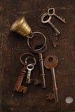 与响铃的铁钥匙在金属背景 免版税库存照片