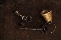 与响铃的铁钥匙在金属背景 免版税库存图片