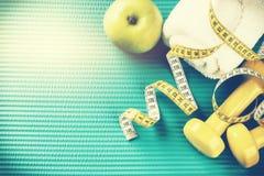 与哑铃、测量的磁带和毛巾的健身背景 Hea 免版税库存照片