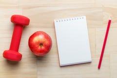 与哑铃、红色苹果和空白的笔记的健身概念 与拷贝空间的顶视图角度 免版税库存照片