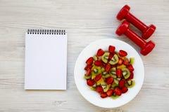 与哑铃和笔记本,顶视图的新鲜水果沙拉 平的位置 免版税图库摄影