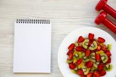 与哑铃和笔记本,顶视图的新鲜水果沙拉 平的位置 库存照片
