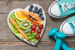 与哑铃教练员和食物的健康饮食和体育概念 免版税库存图片